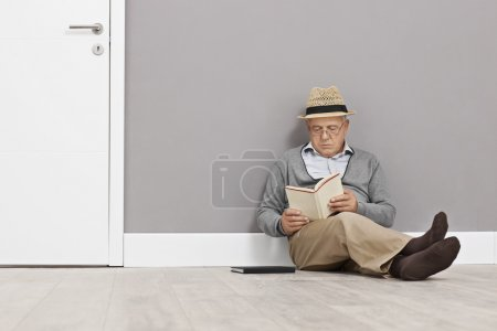 Photo for Senior gentleman reading a book seated on the floor and leaning against a wall next to a white door - Royalty Free Image