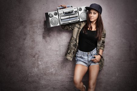 Photo for Teenage girl carrying a ghetto blaster over her shoulder and leaning against a rusty gray wall - Royalty Free Image