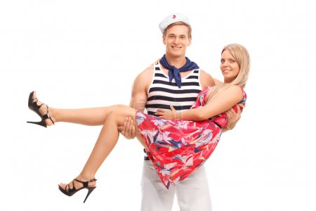 Photo for Young male sailor carrying his girlfriend in his arms and both looking at the camera isolated on white background - Royalty Free Image