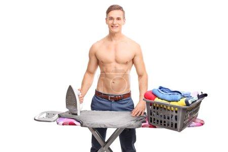 Photo pour Jeune homme torse nu posant derrière une planche à repasser avec un panier plein de vêtements sur elle isolé sur fond blanc - image libre de droit