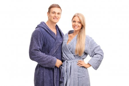 Young couple in blue bathrobes hugging