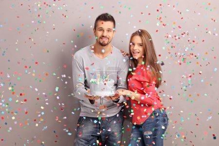 Young joyful couple holding a birthday cake