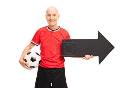 Senior man holding football and arrow