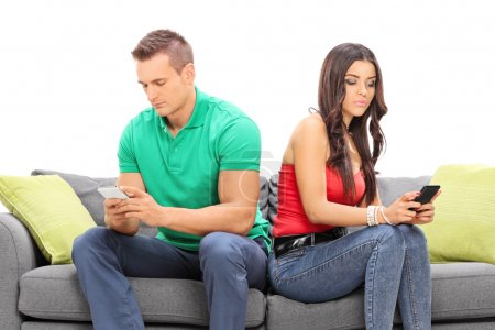 Photo for Young couple looking at their cell phones and ignoring each other seated on a gray sofa isolated on white background - Royalty Free Image
