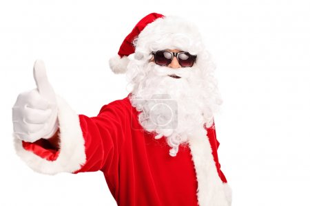Photo for Cool Santa with black sunglasses giving a thumb up and looking at the camera isolated on white background - Royalty Free Image