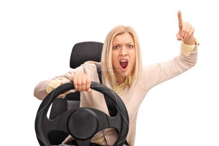 Photo pour Femme en colère prétendant conduire et criant vers la caméra isolée sur fond blanc - image libre de droit