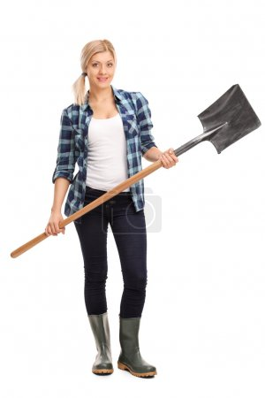 Woman in rubber boots holding a shovel