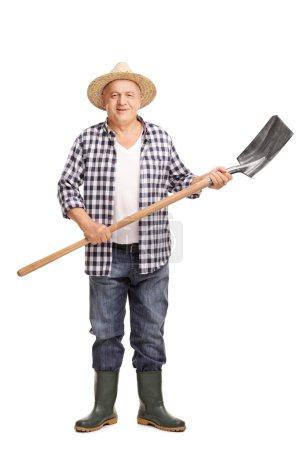 Mature agricultural worker holding a shovel