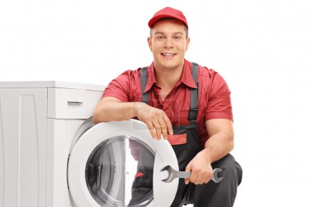 Young cheerful plumber holding a wrench
