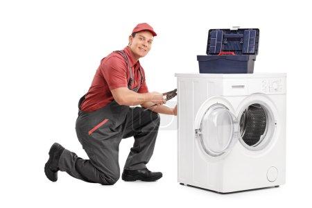 Young repairman fixing a washing machine