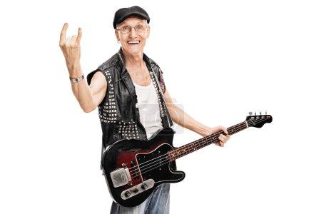 Photo pour Plan studio d'un vieux rocker punk tenant une basse et faisant un geste rock isolé sur fond blanc - image libre de droit