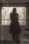 Blurred old vintage picture of a lonely girl in a train looking through the window.