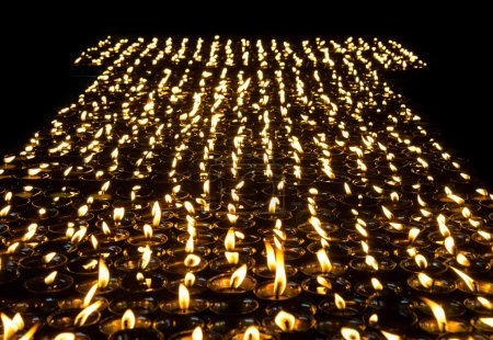 Photo for Lighted candles lined up in a row and glow in the dark space. Monastery in Nepal. Tibet, the Himalayas. - Royalty Free Image