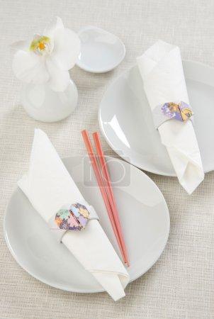 Photo pour Décor anneaux de serviette origami coeur en papier sur une plaque blanche avec baguettes pour sushi - image libre de droit