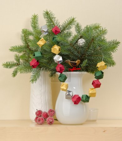 Photo for Christmas interior decoration white vase with fir branches with a garland - Royalty Free Image