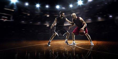 Photo pour Deux joueurs de basket-ball en action dans la salle de gym - image libre de droit