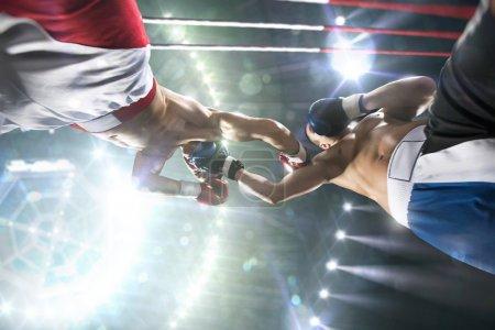 Photo pour Deux boxeurs professionnels se battent sur la grande arène - image libre de droit