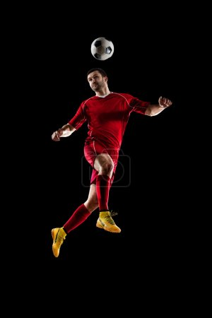 Photo for Football soccer player in action  isolated on black background - Royalty Free Image