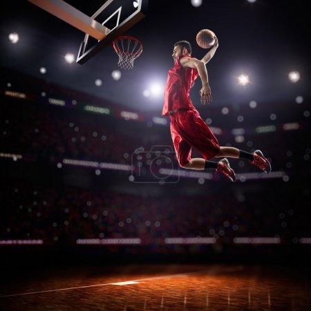 Photo pour Joueur rouge de basket-ball dans l'action dans la gymnastique - image libre de droit