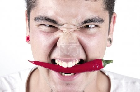 Photo for Young man having fun, holding red hot chilly pepper in mouth. - Royalty Free Image