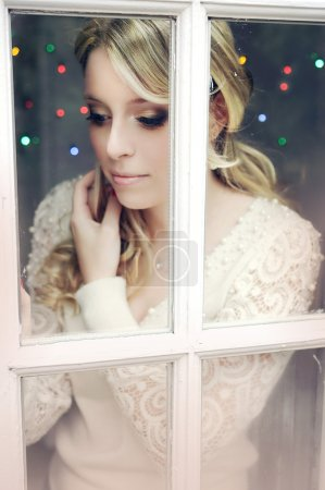 Beautiful blonde young woman with long curly hair and dark evening make-up is standing by the window and looking down, away from the camera.