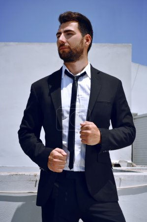 Photo for Attractive Spanish looking young man with a beard and dark hair and eyes is wearing a black suit and tie with a white shirt. - Royalty Free Image