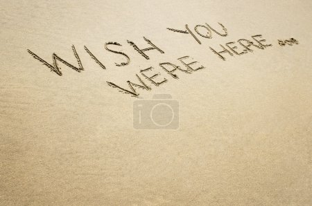 Words wish you were here written in the sand.