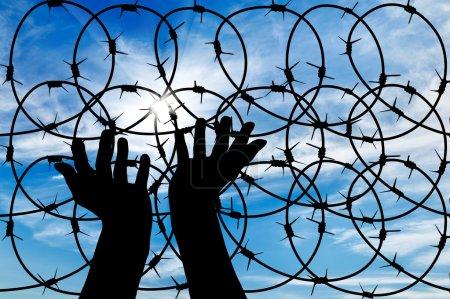 Photo pour Concept des réfugiés. Silhouette d'une main tendue au soleil dans le ciel fond fil barbelé - image libre de droit
