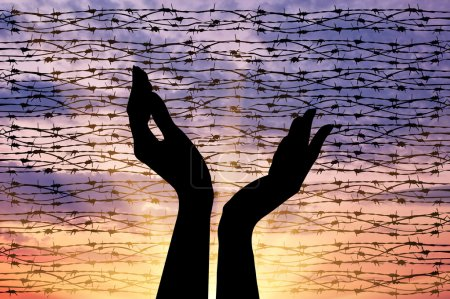 Photo for Concept of the religion of refugees. Silhouette outstretched arms to the sky against a background of barbed wire at sunset - Royalty Free Image