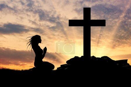 Photo pour Concept de religion. Silhouette d'une femme priant devant la croix au coucher du soleil - image libre de droit