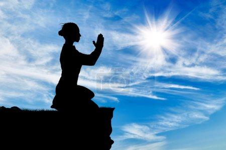 Photo pour Silhouette de femme priante sur le dessus contre le ciel nuageux - image libre de droit