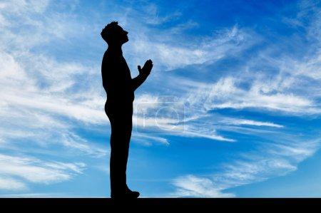 Photo pour Silhouette de l'homme priant dans le ciel en regardant le fond du ciel - image libre de droit