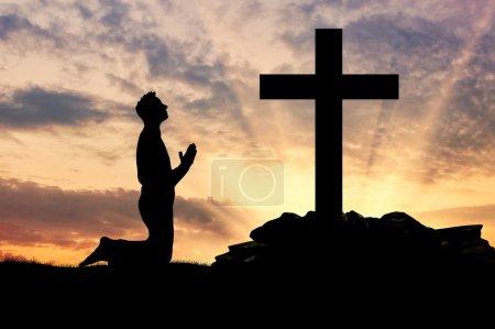 Photo pour Concept de religion. Silhouette d'un homme priant devant une croix au coucher du soleil - image libre de droit
