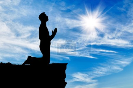 Photo pour Silhouette d'homme priant en haut contre le beau ciel nuageux - image libre de droit