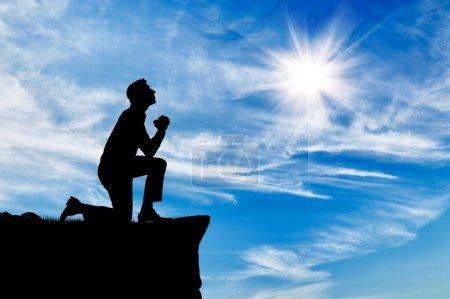 Photo pour Silhouette de l'homme priant en haut contre le beau ciel nuageux - image libre de droit