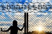 Silhouette of a refugee near the fence