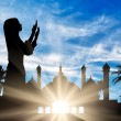Concept of the Islamic religion. Silhouette of praying woman against the backdrop of the town hall at dawn