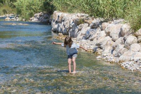 Little girl crossing a river