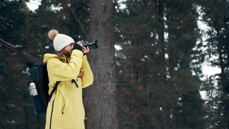 Photo pour Une fille avec un sac à dos et un anorak jaune photographie le paysage sur un appareil photo professionnel. - image libre de droit