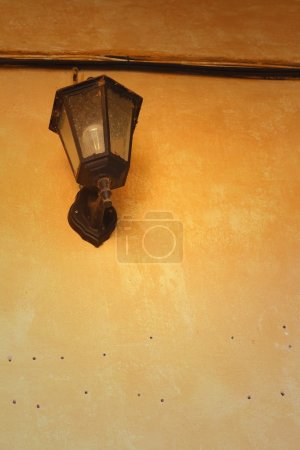 A lamp on a wall on brown background....