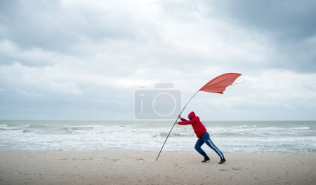 On the shore of stormy sea person struggling with the wind. The red flag indicates the strength of the wind.