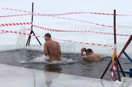 Photo for Winter ice swimming sport, a two European man people swimming in the ice hole water with splashes on a Sunny frosty winter day, healthy lifestyle - Royalty Free Image