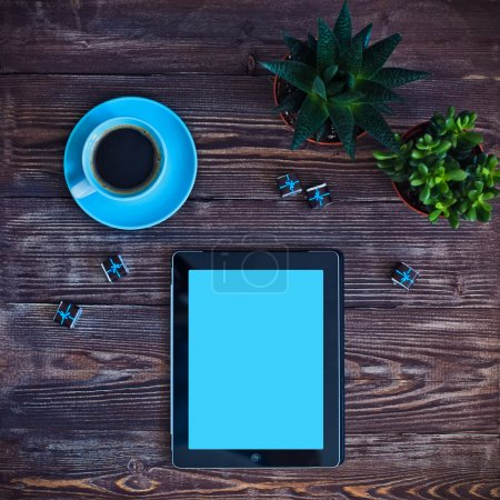 Photo for Digital tablet computer with cup of coffee and succulents on old wooden desk. Simple workspace or coffee break with web surfing. - Royalty Free Image