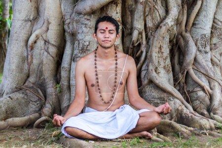 Photo pour Un jeune brahmane hindou est assis en méditation sous un banyan . - image libre de droit