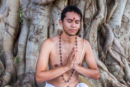 Photo pour Un jeune brahmane est assis en méditation sous un banyan . - image libre de droit