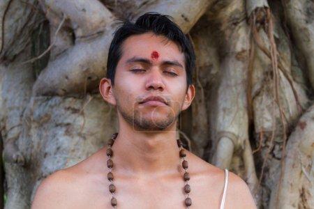 Photo pour Un jeune brahmane est assis en méditation sous un banyan en Inde - image libre de droit