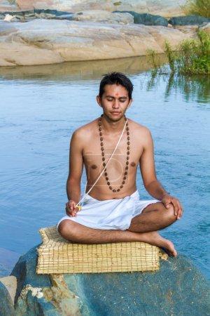 Photo pour Un jeune brahmane hindou est assis en méditation sur une rive de rivière . - image libre de droit