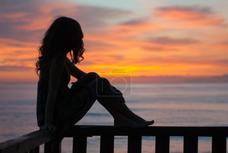 Photo for Young woman sitting on a balcony by the sea and waiting the sunrise - Royalty Free Image
