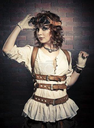 Photo pour Belle fille rousse avec des lunettes steampunk debout sur un fond de mur de brique, des lunettes atinge et en regardant la caméra - image libre de droit