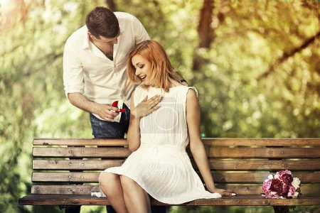 Photo for Man holding red box with ring making propose to his girlfriend outdoors. - Royalty Free Image
